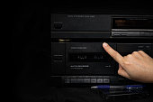 Woman hand inserting compact cassette tape in old player audio are retro technology