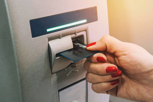 woman hand inserting credit card to ATM. girl gets paid from an ATM. The card comes out of the terminal. stock photo