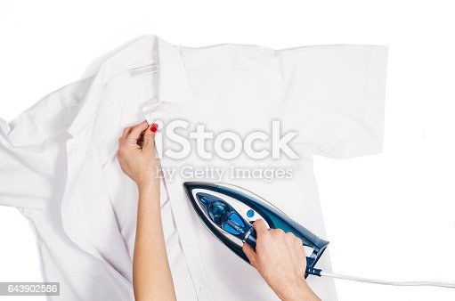 645276668 istock photo Woman hand ironing clothes top view isolated on white background 643902586