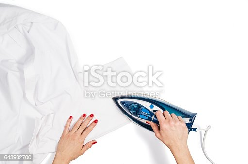 645276668 istock photo Woman hand ironing clothes top view isolated on white background 643902700