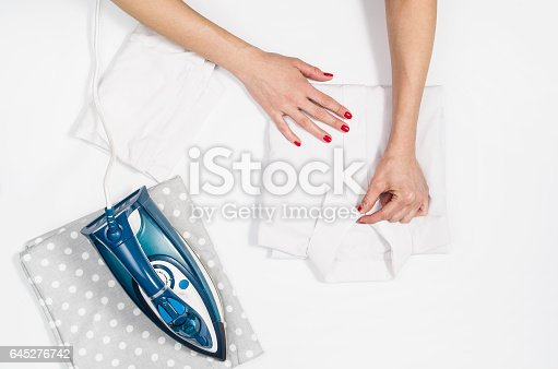 645276668 istock photo Woman hand ironing clothes top view isolated on white background 645276742