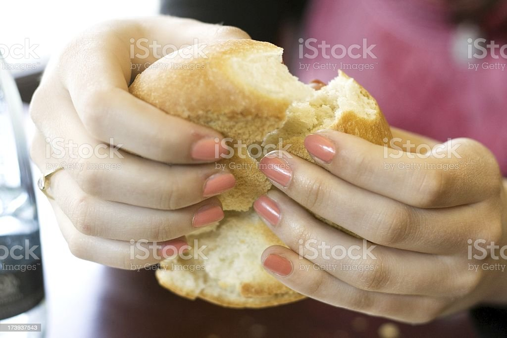 woman hand is breaking the bun into two stock photo
