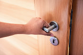 istock Woman Hand is Holding Door Knob While Opening a Door in Bedroom, Lock Security System and Access Safety of Doorway., Interior Design of Doorknob Entering to Accessibility Private Room 1179514454