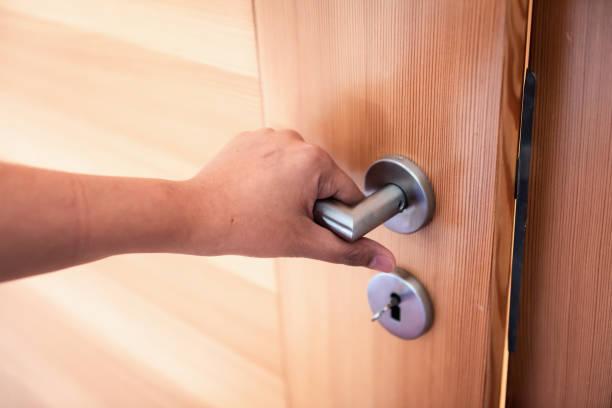 여자 손은 침실에 문을 열고 있는 동안 문 손잡이를 잡고, 잠금 보안 시스템 및 출입구의 액세스 안전., 접근 개인 방에 들어가는 문 손잡이의 인테리어 디자인 - 문손잡이 뉴스 사진 이미지
