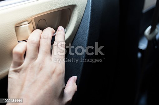 Woman hand is holding the door inside the car