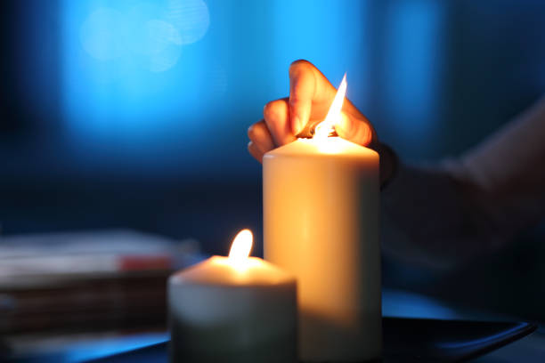 Woman hand lighting candle in the night at home stock photo
