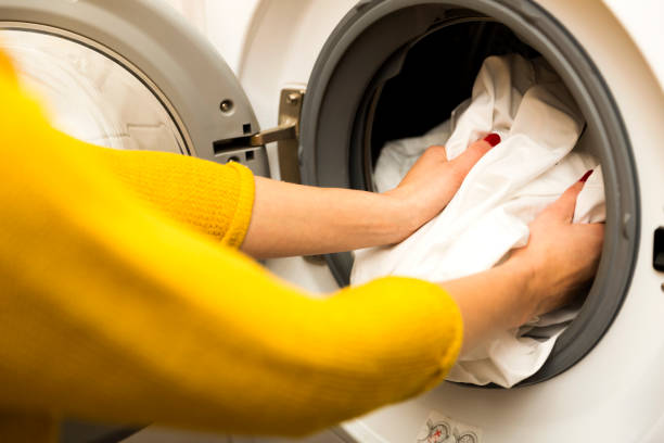 frau hand laden schmutzige wäsche in der waschmaschine - fleckenentferner stock-fotos und bilder