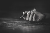 istock Woman hand of a drug addict and a syringe with narcotic syringe lying on the floor, Overdose, drug concept. 1127316487