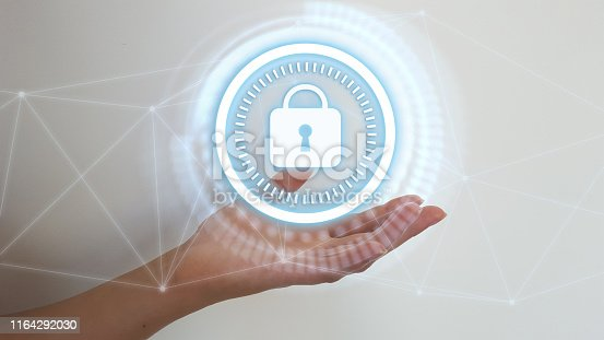 istock Woman hand on blurred background holding digital padlock security interface to protect datas 1164292030