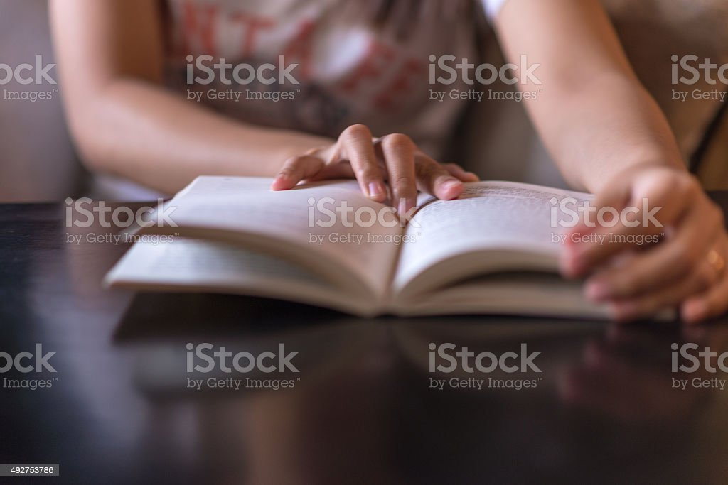 Woman hand on the opened book stock photo