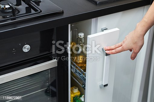 Woman hand open kitchen storage cabinet in modern interior