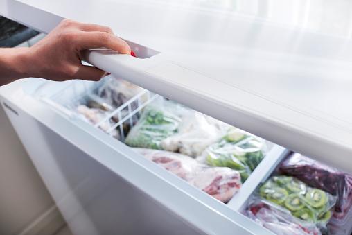Woman hand opening a refrigerator door.