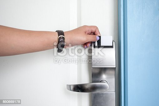 Woman hand opening hotel room door by keycard