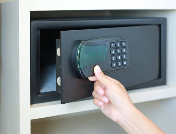 Woman hand opens a safe hidden in the wardrobe at the hotel. - foto stock
