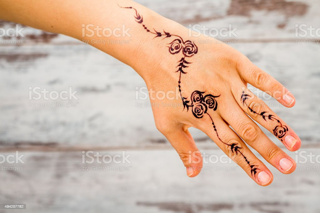 4e4ec96ac Woman Hand Painted with Floral Figures Using Black Henna - Stock image .