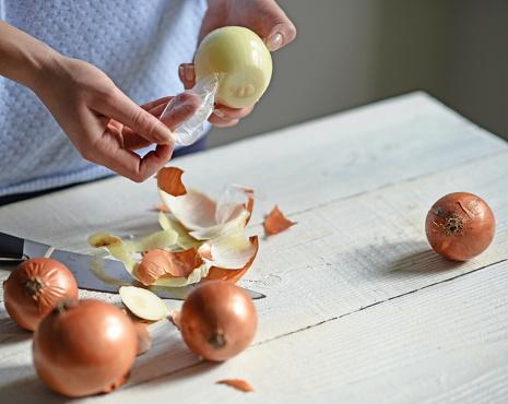 Woman hand peel fresh onion on white table
