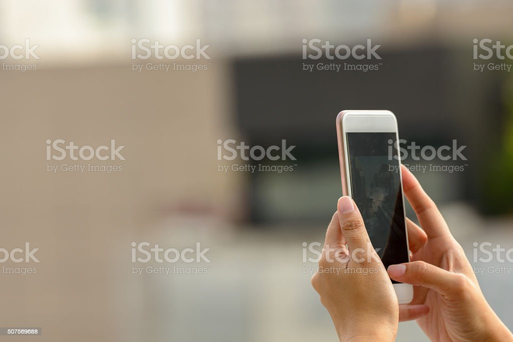 Woman hand photographing using mobile phone outdoors stock photo