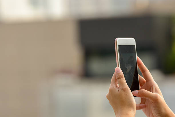woman hand photographing using mobile phone outdoors - photo messaging stock photos and pictures