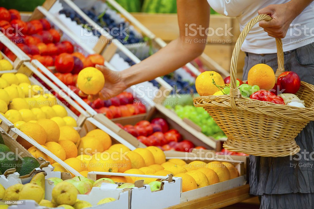 Woman hand picking grapefruit at grocery store royalty-free stock photo