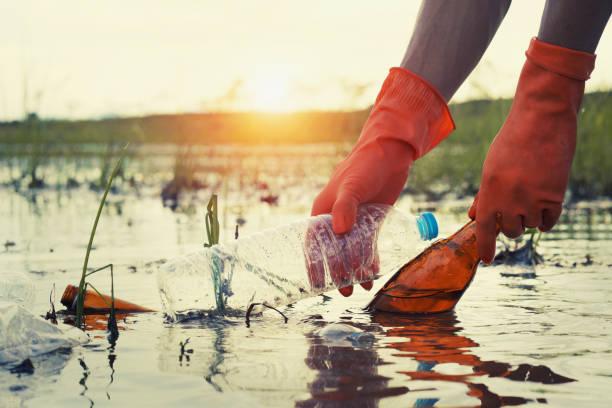 Frau Hand holen Müll Kunststoff für die Reinigung am Fluss mit Sonnenuntergang – Foto