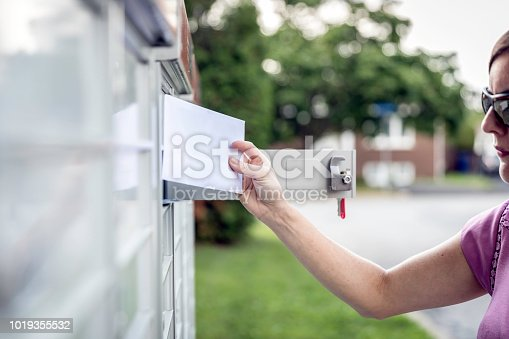 istock Woman hand Picking up the Mail at Postal Mailbox 1019355532