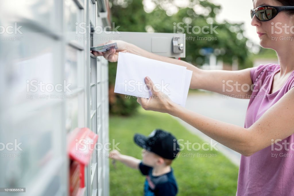 Woman Hand Picking Up The Mail At Postal Mailbox With Young Boy