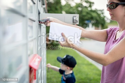 istock Woman hand Picking up the Mail at Postal Mailbox with Young Boy 1019355528