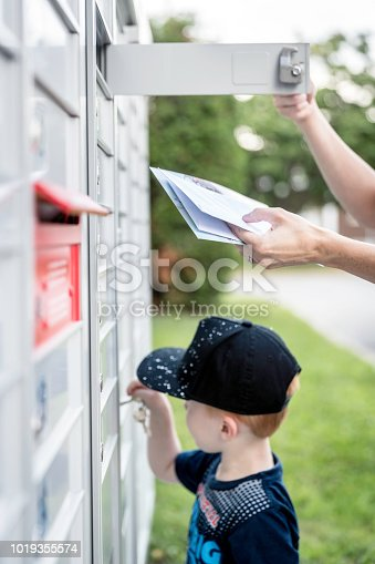 istock Woman hand Picking up the Mail at Postal Mailbox with Young Boy 1019355574