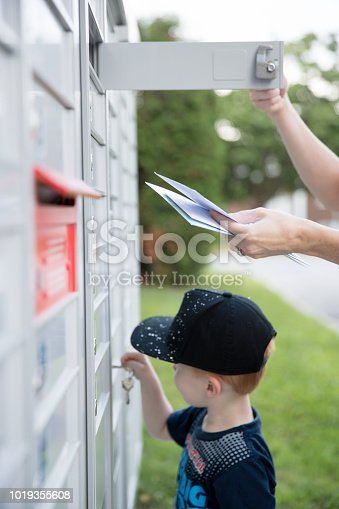 istock Woman hand Picking up the Mail at Postal Mailbox with Young Boy 1019355608