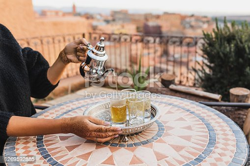Woman hand pouring traditional moroccan mint tea in glasses. Vintage silver tray and teapot. Round mosaic table. Morocco hospitality.
