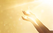istock Woman hand praying for blessing from god on sunset background 638136458