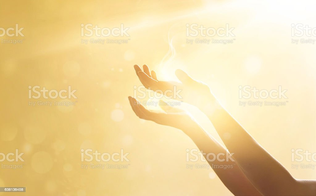 Woman hand praying for blessing from god on sunset background stock photo