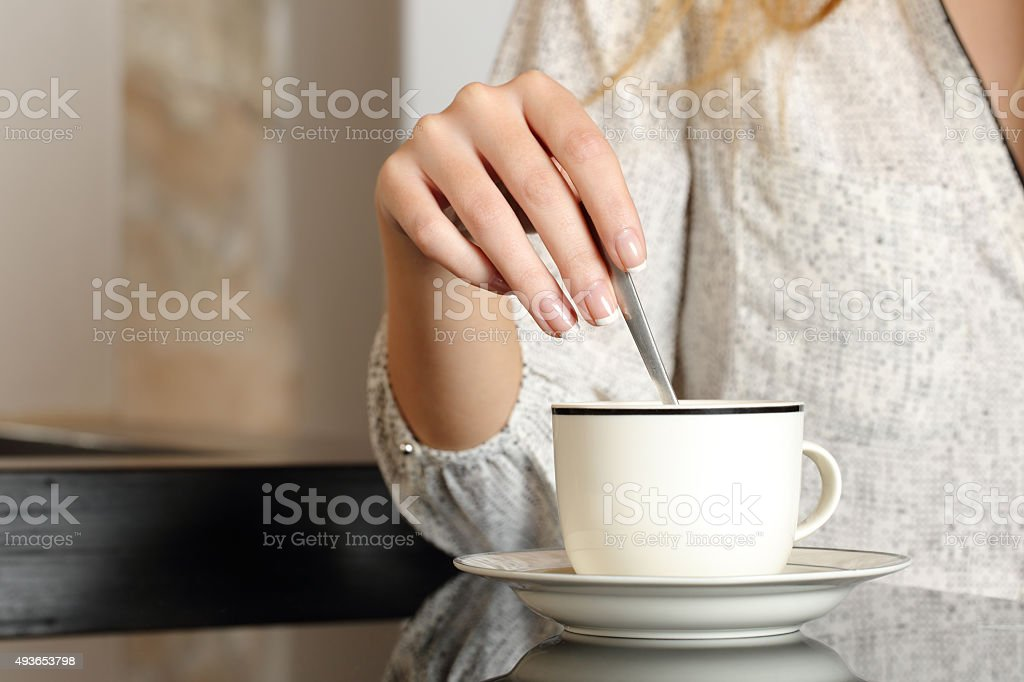Woman hand preparing a cup of coffee stock photo