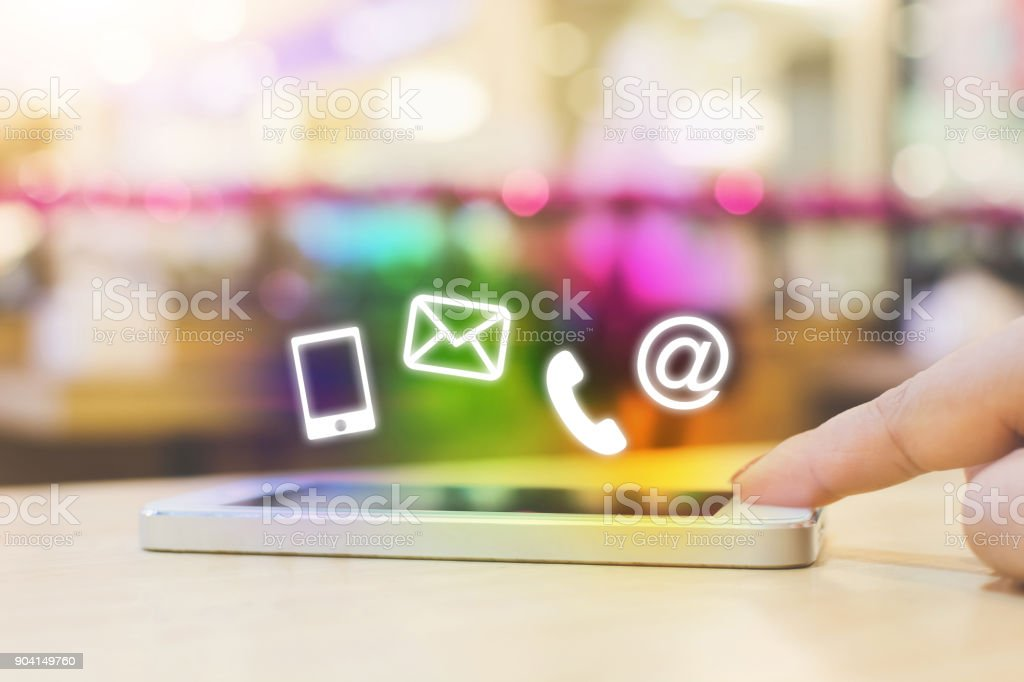 Woman hand pushing button smartphone, Business connection contact us and call center customer service concept, Icon mobile phone, email envelope, telephone and e-mail address stock photo