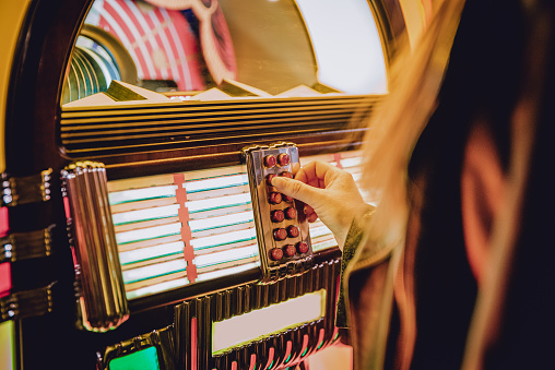 woman hand pushing buttons to play song on old Jukebox, selecting records