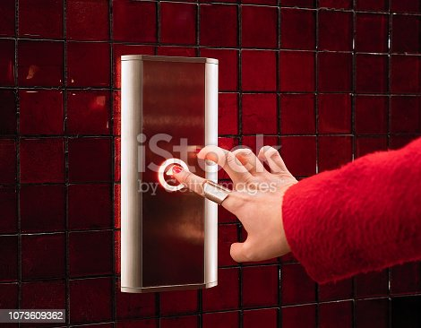 Close-up of woman hand pushing up button in red elevator with red coat on