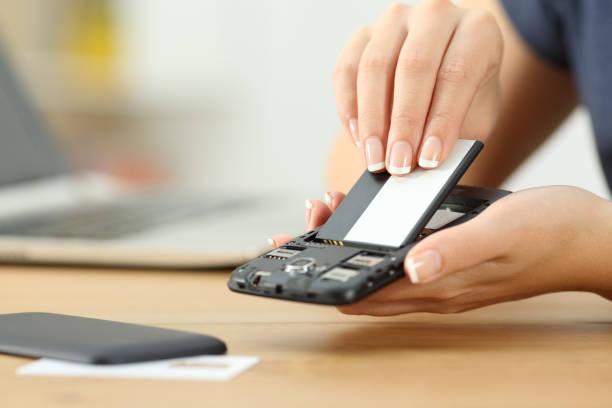 hand der frau, eine batterie in ein smart phone - batterie stock-fotos und bilder