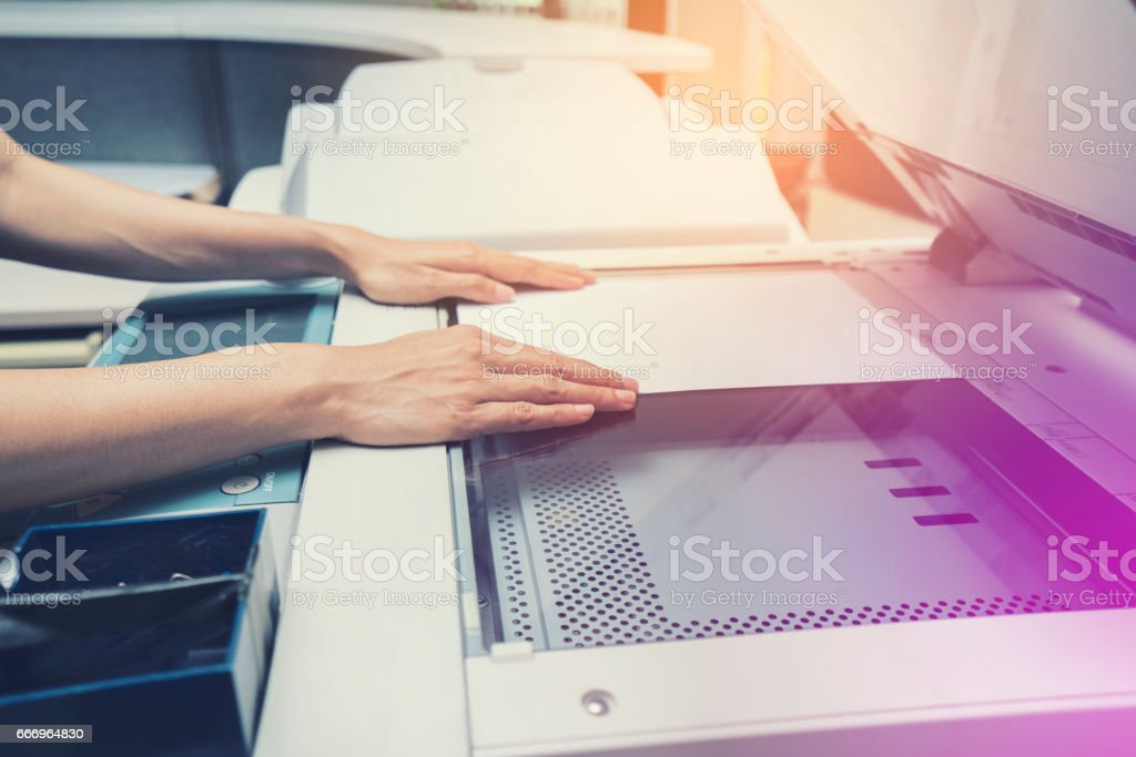 woman hand putting a sheet of paper into a copying device stock photo