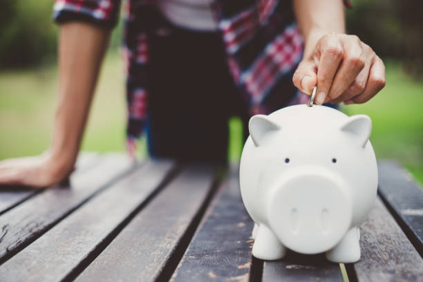 woman hand putting coin into piggy for saving money wealth and financial concept. - piggy bank stock photos and pictures
