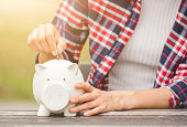 istock woman hand putting coin into piggy for saving money wealth and financial concept. 995991166