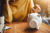 istock woman hand putting money coin into piggy for saving money wealth and financial concept. 1049807888