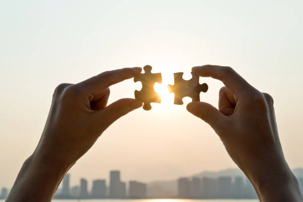 Woman hand putting puzzle pieces together in sunset stock photo
