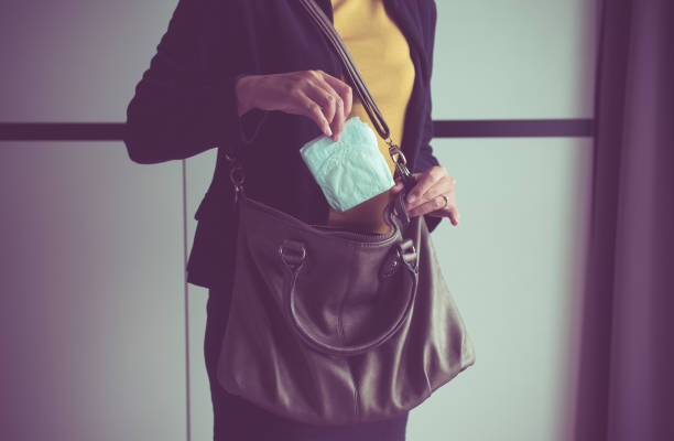 Woman hand putting sanitary napkins in handbag,White menstrual pad Woman hand putting sanitary napkins in handbag,White menstrual pad styles stock pictures, royalty-free photos & images