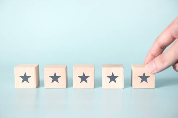 Frau Hand setzen Holz Fünf-Sterne-Form auf blauem Hintergrund. – Foto
