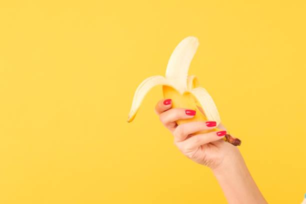 plátano del peel de asimiento de la esmalte de uñas rojo de mano de la mujer amarillo - foto de stock