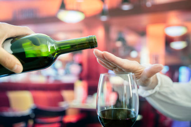 Woman hand rejecting more alcohol from wine bottle in bar stock photo
