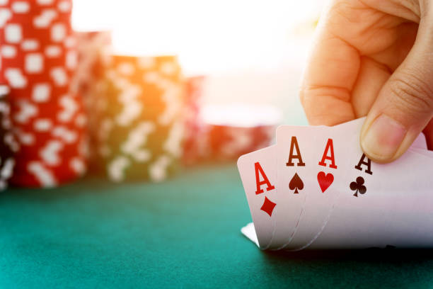 Woman hand revealing four aces stock photo