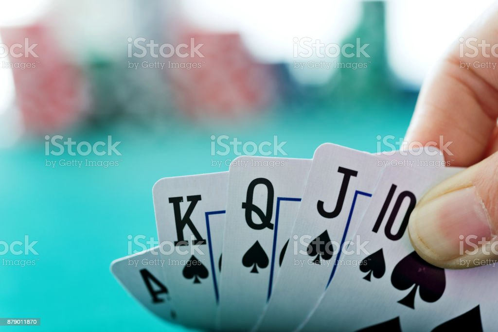 Woman hand revealing royal flush stock photo