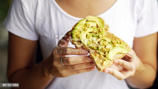 istock woman hand show eating avocado bread cheese toast white t-shirt background 891931888
