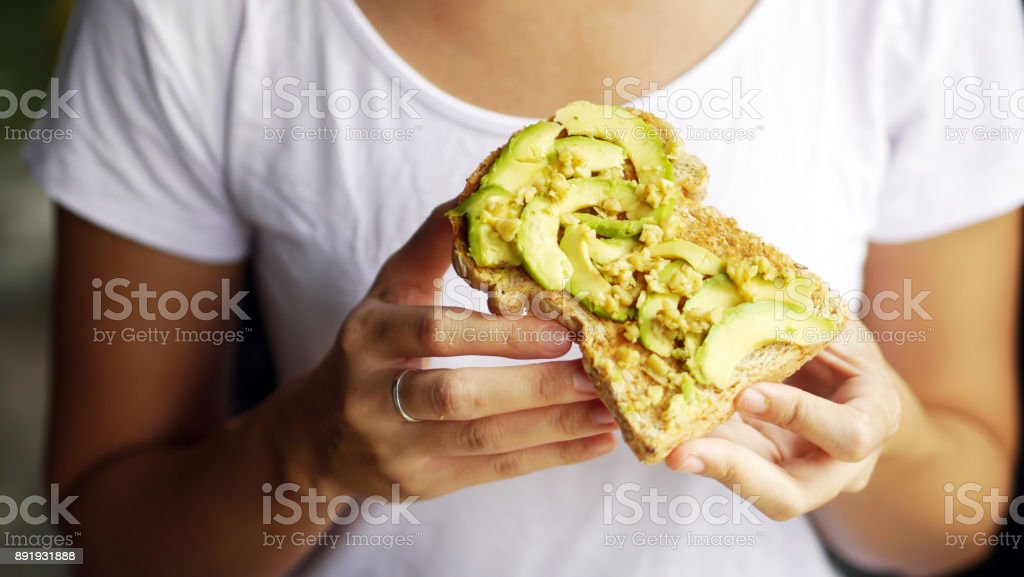 woman hand show eating avocado bread cheese toast white t-shirt background stock photo